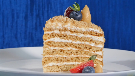 Layer cake with cuted strawberry and blueberries on plate. Summer berry cake. Piece of Multi-layered Berry and Pistachio Mousse Cake