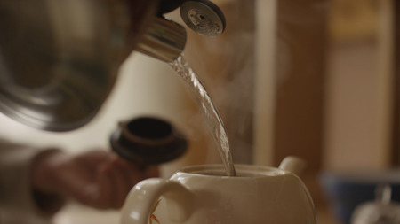 Woman pours boiling water into the cup and brew tea in a tea bag. The woman pours hot water into the teapot with tea Stock Photo