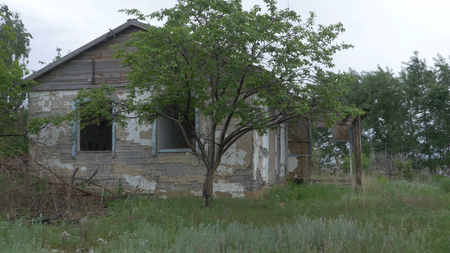 An old, abandoned house in the village, on a background of trees. Abandoned house near Donetsk. Destroyed houses and ruins, mechanisms Ukraine