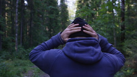 resting heart rate: Young man wearing a hat in the woods. Athlete came into the forest to do sports Stock Photo