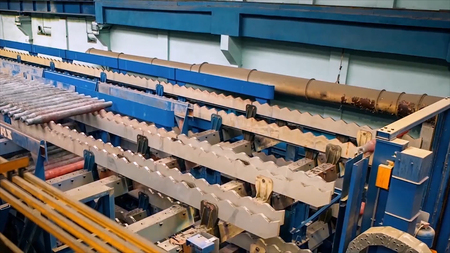 Manufacture of rails for trains and freight wagon, boxcars. Rail manufacturing plant. Stack of steel round bar - iron metal rail lines material for industry construction in warehouse. the big press. Animation