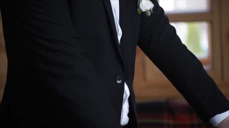 Man buttoning on a black jacket. Wedding details - elegant groom dressed wedding tuxedo costume is waiting for the bride. businessman buttoning jacket, getting dressed. Groom buttons jacket