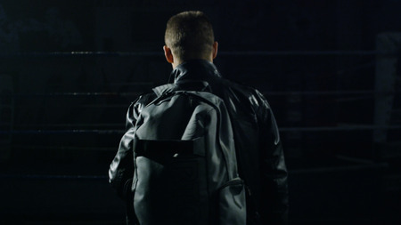 Man in a jacket and bag in the gym. Man going with bag after training. Man going to the gym Banco de Imagens