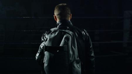 Man in een jas en tas in de sportschool. Man gaat met tas na de training. Man gaat naar de sportschool