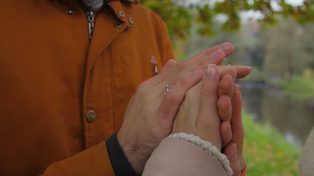 A man warms womans hands. Bride and groom holding hands and warm each other in a park. Man and woman holding hands. warming hands.