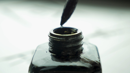 Female hand dunks brush in a jar of ink for drawing close up. Chinese Old-fashioned Paint Brushes with Selective Focus. Detail of a chinese brush while drawing a line in light back 4K