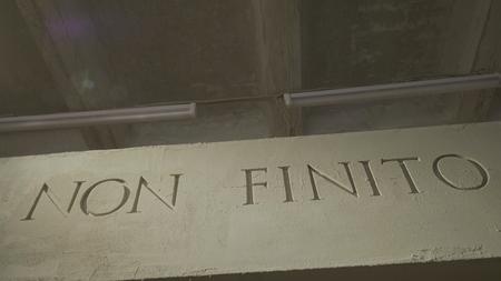La inscripción que significa que no es el final en la pared gris. Texto aislado de NON FINITO, acrónimo del antiguo Imperio Romano 4K Foto de archivo