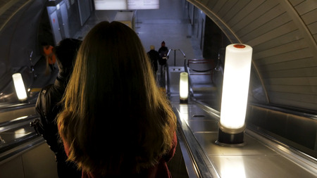 Rear view of girl girl down the escalator in the subway. Woman coming down to the metro station through the escalator tounel. woman riding up an escalator in a metro station 4K