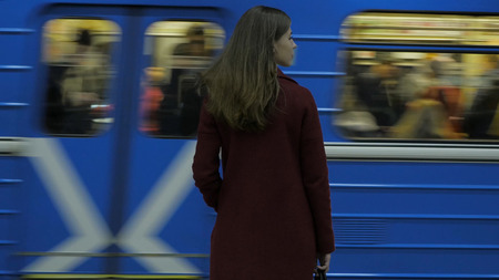 Girl waiting for arriving train at the subway station. Rear view of girl waiting at train station. Train arrives 4K