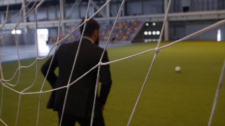 Businessman play footbal on green field like a goalkeeper. Close up of a man wearing formal suit at the field while holding a soccer ball HD