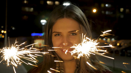 Young beautiful happy smiling girl holding sparkler on the street. Holiday concept. Girl with sparklers in the street