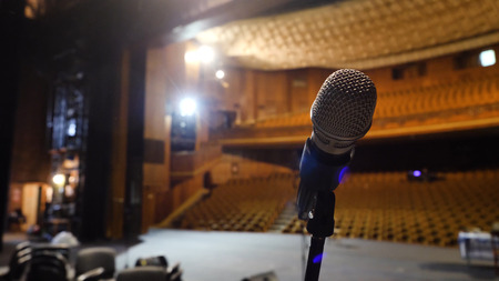 Microphone on the stage and empty hall during the rehearsal. Microphone on stage with stage-lights in the background. Microphone on the stage in the empty hall.