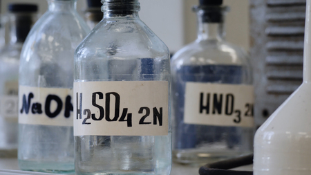 Bottles of solutions stored on shelf in laboratory. Bottles with chemical solutions of NaOH, H2so4 and HNO3. Sulfuric acid, sodium hydroxide, nitric acid
