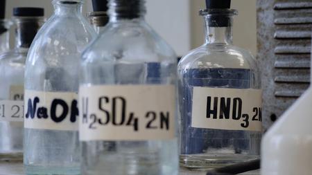 Flessen oplossingen opgeslagen op plank in het laboratorium. Flessen met chemische oplossingen van NaOH, H2so4 en HNO3. Zwavelzuur, natriumhydroxide, salpeterzuur.