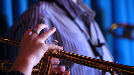 cornet: Trumpet player. Trumpeter hands playing brass music instrument close up