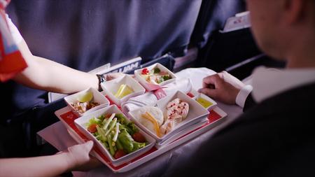 青い背景に飛行機の食べ物とトレイを保持スチュワーデスの中間部。スチュワーデスは、昼食、ビジネスマン、ファーストクラス、飛行機上のサー