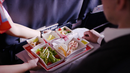 Midsection of stewardess holding tray with airplane food on blue background. Stewardess brought lunch, businessman, first class, high level of service on the plane 스톡 콘텐츠