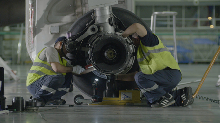 Replacement landing gear. Working staff has been working to repair the chassis of a passenger plane Stock Photo