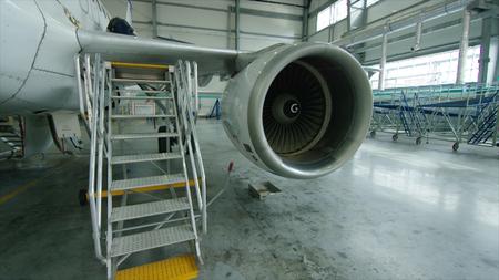 Aircraft engine in the hangar. Airplane turbine detail, plane in hangar. Engine of the airplane under heavy maintenance close up HD