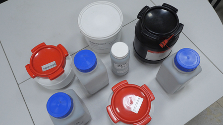 Many bottles of solvents and reagents for cell culture on a shelf in laboratory p