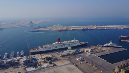 Huge cruise ship is on the water. Aerial view of Dubai seaport United Arab Emirates . Top view of the construction of a water port in Dubai