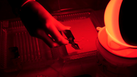 Dark room equipped under photo laboratory. Trays with reagents for printing by hand. Darkroom printing process photographer using enlarger to produce photographic prints. Working in a red dark room. Stok Fotoğraf - 91527891