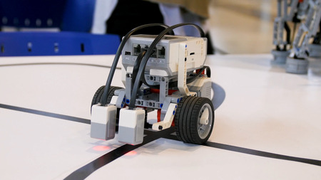 New robot project. Driving over the black tape. Self control with path detector. Electric vehicle robot on wheels during the race