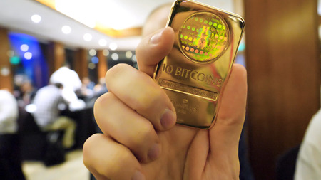 Close up of Male hand and gold bullion with Bitcoin symbol on it. Concept of Cryptocurrency physical bitcoin with gold bar and sunburst effect. BTC gold.