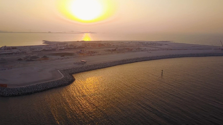 Aerial view of Dubai seaport United Arab Emirates . Top view of the construction of a water port in Dubai at sunset.