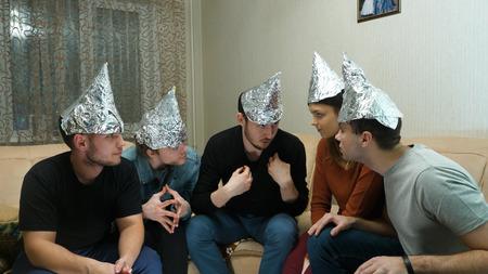 Amigos en papel de aluminio en la cabeza de la casa. Reunión de amigos sobre escuchar sus ideas de civilizaciones extraterrestres Foto de archivo