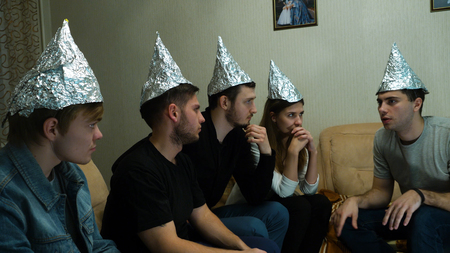 Friends in foil on the head of the house. Gathering of friends about listening to their ideas of extraterrestrial civilizations Standard-Bild