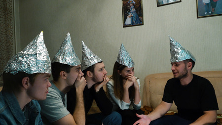 친구들은 자신의 생각을 두려워하고 외계 문명에서 마음을 보호하기 위해 머리에 호일을 붙입니다. UFO는 사람들의 생각을 읽고 호일은 그것을 할 수 없습니다. 스톡 콘텐츠 - 92214973