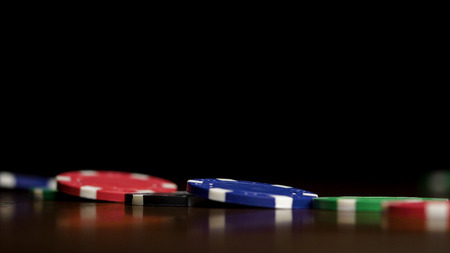 Poker chips stand in a row on a black background, a Domino effect. Playing poker chips are on the table, a symbol of casino. Stock Photo