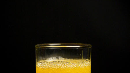 Pouring Orange Drink. Slow Motion. Carbonated orange drink is poured into a glass. Pouring orange juice soda in glass in slow motion, black background.