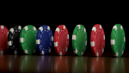 Playing poker chips in reflective black background. Poker chips poker chips stand in a row with dark background. Colorful poker chips standing with white light and black background.