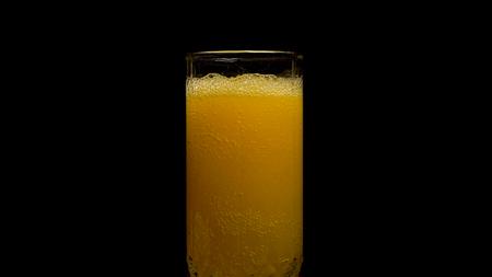 Orange soda large glass, overflowing glass of orange soda closeup with bubbles isolated on black background. Pouring Orange Drink. Slow Motion. Carbonated orange drink is poured into a glass. Pouring orange juice soda in glass in slow motion, black background