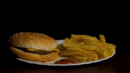 Hamburger with fries isolated on black background. French fries on white plate with ketchup and cheese sauce isolated on black background. Top view.Chicken burger plate with french fries and salad. Banque d'images - 93113061