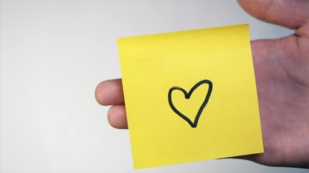 Mans hand put blank yellow sticker isolated on a white background. I Love You H Stock Photo
