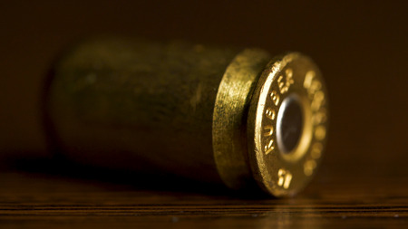 bullet macro with limited dof on a black background, 9mm full metal jacket. Bullet isolated on black background with reflexion. close up gun bullets. Weapon Cartridge case sleeve background texture 9mm. Stock Photo