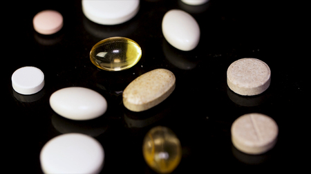 Various colorful pills on black background. Pile of several medicines on black background. Colorful pills over dark background. white pills on black glass background. medical pharmacy.