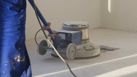 Man polishing marble floor in modern office building. The people cleaning floor with machine. Man polishing floors.