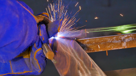 Worker with protective mask welding metal welding, welder, steel . A man welds a metal with a welding machine.