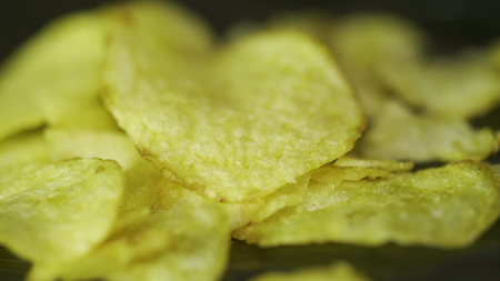Rotating potato chips close up, macro view food background. Close-up of yellow delicious chips randomly lying on a table. Tasty potato chips. Potato chips, close-up
