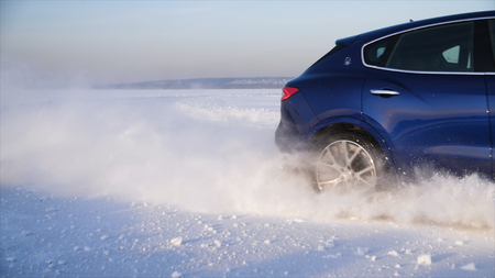 Car with winter tyres installed on light alloy wheels in snowy outdoors road. A car driving down a snowy road during winter. Car drives on a snowy road