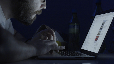 Side view of man typing messages on laptop keyboard in dark room. Anonymous male on a laptop at night. Concept of internet addiction. A man is a laptop dark room a man is working in a dark room