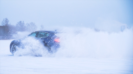 Car making u-turn in the snow. Sports car drives in the snow. Blue crossover does tricks in the snow Archivio Fotografico