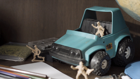 Toy soldier. Plastic Green Tracked Army Vehicle on a battlefield. Miniature toy soldiers.