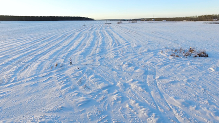 Aerial view on man walking in taiga or snow field. Footage. Siberia, Endless Taiga. A man skiing wanders through the forest in deep snow.