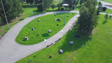 Road near the green park, top view. Green Park and its vast lawns on a sunny spring day. Clip. Aerial from flying drone of a city park with walking path and green zone trees. Cyclist in the Park Stock Photo