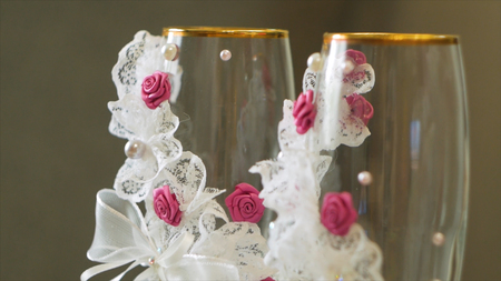 Close up champagne glasses with pink champagne and gold sugar on the rim. Video. Glasses for a wedding on a gray background